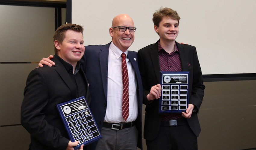 Mount Royal University President and Vice-Chancellor Tim Rahilly, PhD, centre, celebrates with Employment Preparation Certificate graduates Austin Repetwoski, left, and Nicholas Slade at the 2019 graduation event.