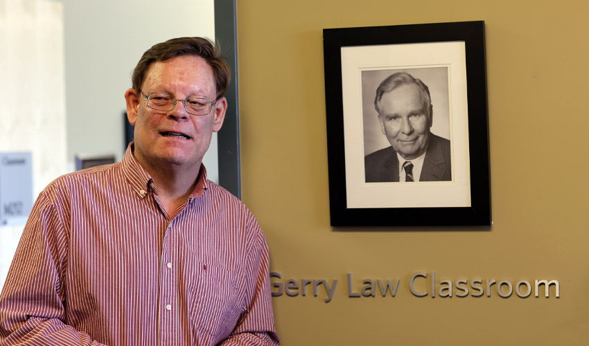 Jaime Law poses with a photo of his father, Gerry, at the opening of the Gerry Law Classroom.