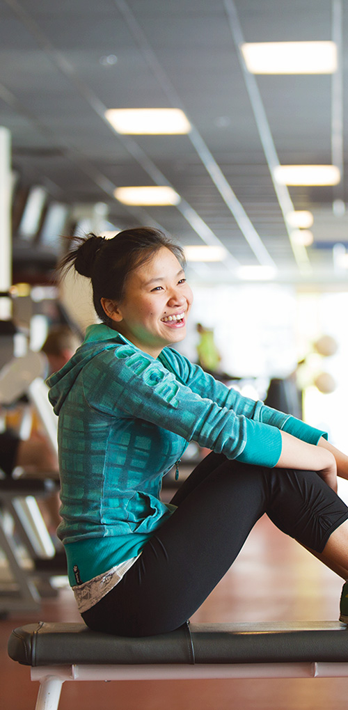 Student taking a break on a bench in the gym at MRU Recreation.
