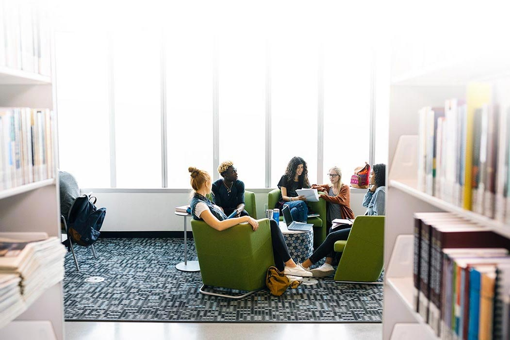 A diverse group of students gathered in a seating area of a bright library.