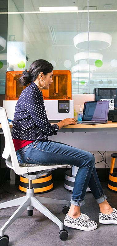 Female student at a desk, working on a laptop with a 3D printer in the background.