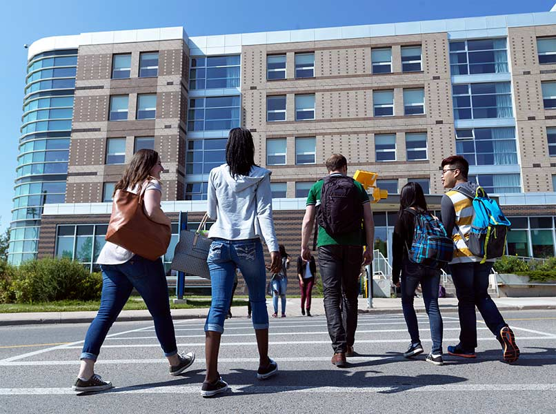 Diverse row of students, walking across a marked intersection over to a West Residence building.
