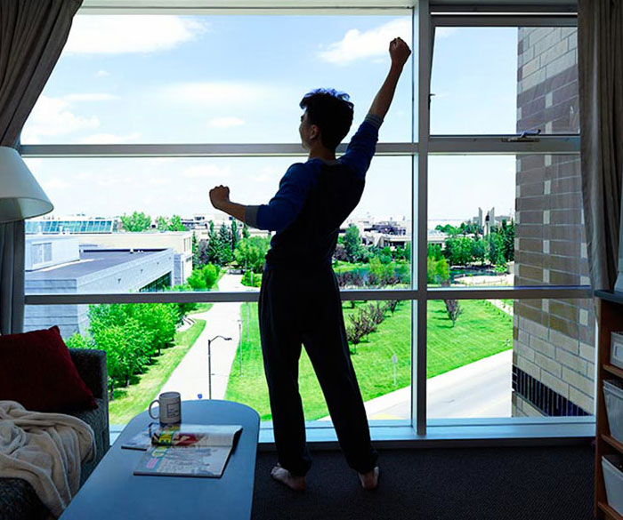 Student stretching their arms up in front of a floor to ceiling window, with a clear view of campus from their Residence suite.