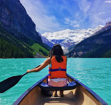 Female with dark hair, paddling a canoe on Lake Louise, Alberta, with a snowy mountain scene in the background.