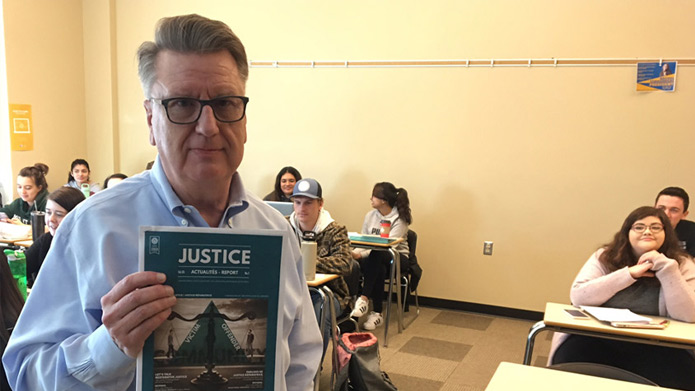 Doug King, PhD, holding a copy of the Canadian Criminal Justice Association's journal Justice Report in a classroom full of students