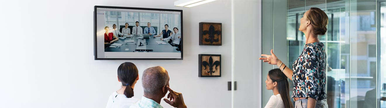 A group of business professionals in a meeting room talking to people via video conference.