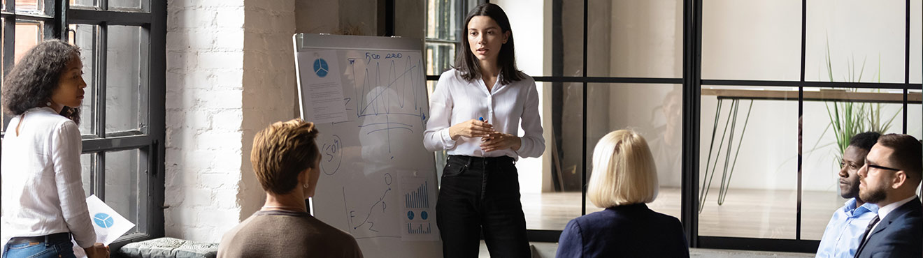 A young professional stands by a whiteboard covered in notes and charts and speaks to a group of other professionals.