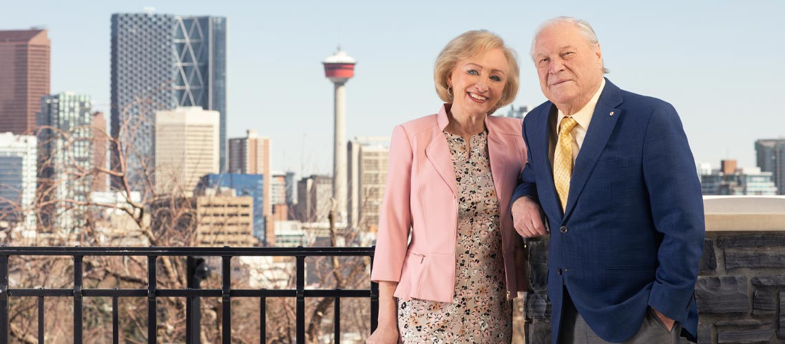 Don and Ruth Taylor standing side-by-side with the City of Calgary in the background.